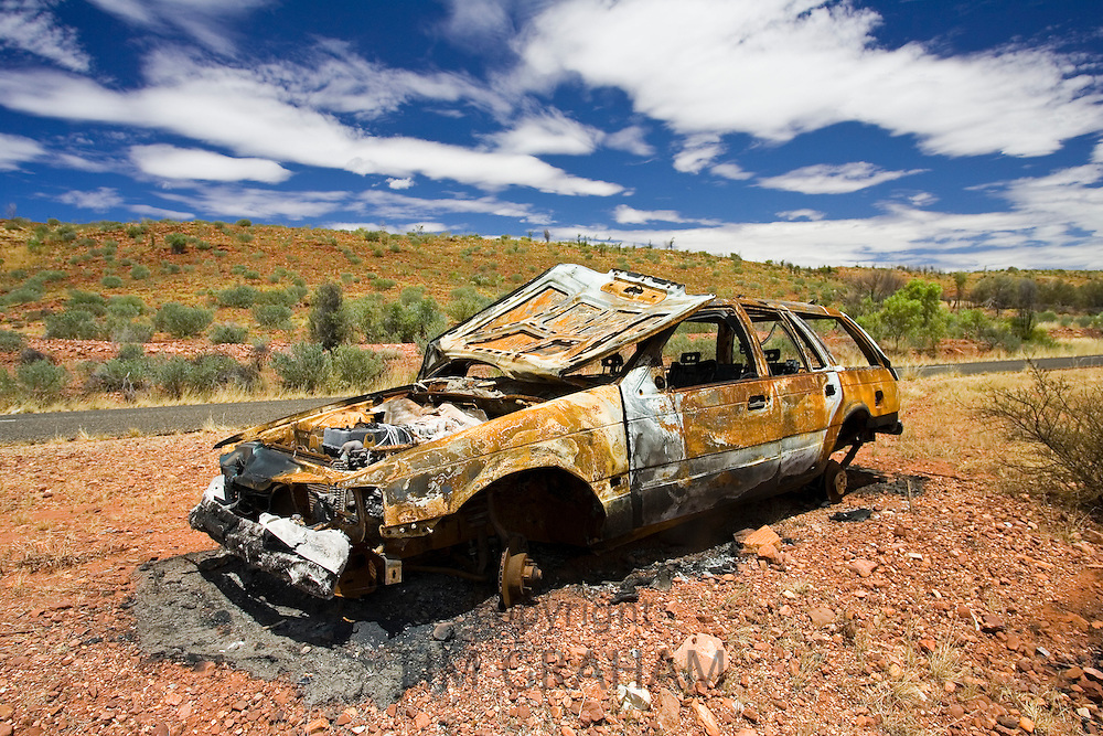 Burnt-out car wreck on road from Alice Springs, Namatjira Drive, Northern Territory, Australia