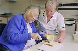 Occupational therapist carrying out a functional assessment on stroke unit observing patient buttering bread,