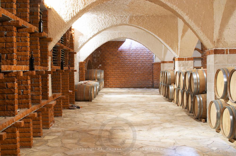 Wine cellar with bottle bins and oak barrels, arched vaulted ceiling. Matusko Winery. Potmje village, Dingac wine region, Peljesac peninsula. Matusko Winery. Dingac village and region. Peljesac peninsula. Dalmatian Coast, Croatia, Europe.