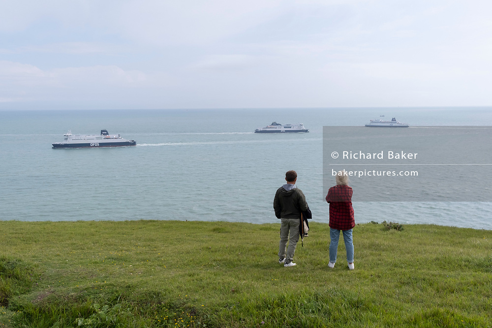 Two walkers watch departing and arriving cross-Channel ferries near Dover Docks,  along the clifftop footpath, near the edge of England's iconic White Cliffs, under threat from chalk and soil erosion, on 27th July, at Langdon Bay, Dover, in Kent, England.