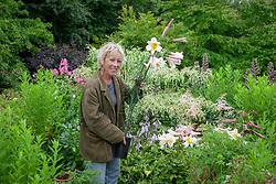 Carol Klein placing pot grown lilies in the garden. Lilium regale