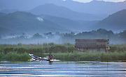 A woman fishes early in the morning in front of the Sin Taung mountains (Elephant Back Mountains) at Inle Lake, Myanmar