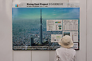 An older Japanese woman reads details of the new Tokyo Sky Tree  on the wall of its construction site. Tokyo, Japan. Monday June 21st 2010. In this image the unfinished telecommunication tower stands at 398 metres high, Upon completion it will measure 634 metres from top to bottom, becoming the tallest structure in East Asia.
