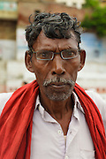 Portrait of an Indian man at Dattatreya Ghat, by the Ganges river, in Varanasi, India.