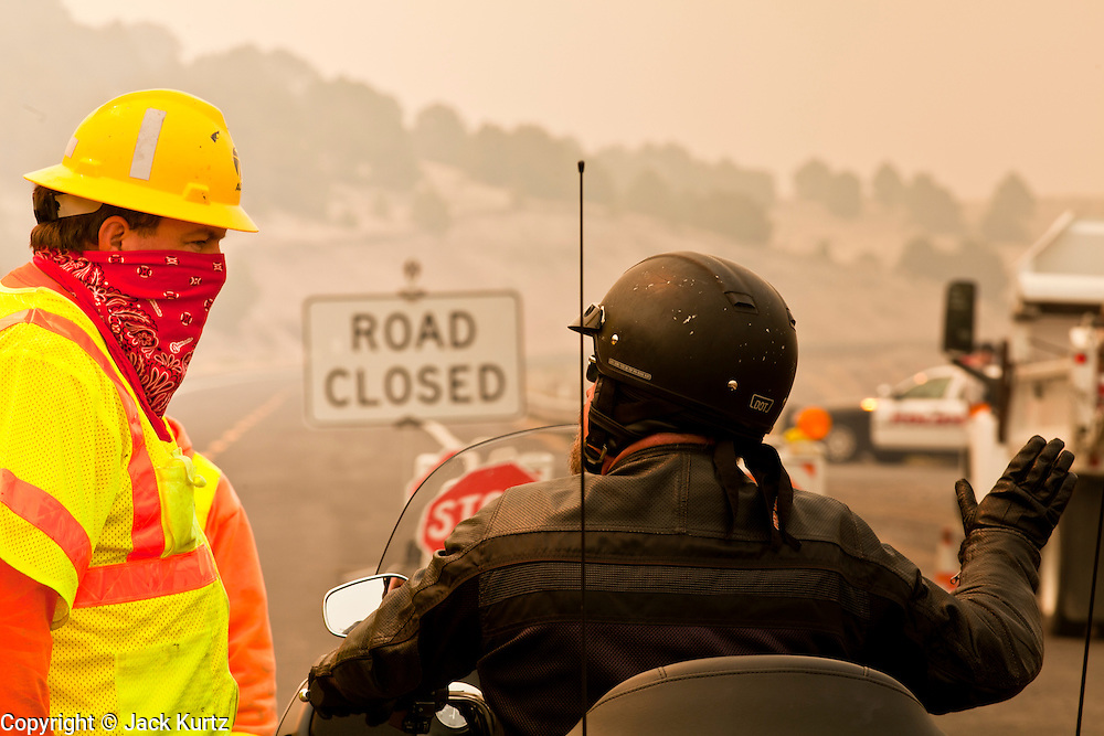 """03 JUNE 2011 - SPRINGERVILLE, AZ: Mike Taylor (CQ) from ADoT, talks to Ron Grittman, (CQ) from Chino Valley, at a roadblock on Highway 180 at Nelson Reservoir. The road into Nutrioso and Alpine is closed from here to south of Hannigan's Meadow. Grittman was planning on riding his Harley from Chino Valley down 180 to Lordsburg NM and Silver City and back. Now he's looking for a new route. High winds and temperatures have continued to complicate firefighters' efforts to get the Wallow fire under control. The  mandatory evacuation order for Alpine was extended to Nutrioso, about 10 miles north of Alpine and early Friday morning fire was reported on the south side of Nutrioso. The fire grew to more than 106,000 acres early Friday with zero containment. A """"Type I"""" incident command team has been called in to manage the fire.  PHOTO BY JACK KURTZ"""