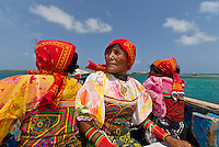 Kuna Indian women in native costume (with Mola embrodery blouses) in a dugout canoe, San Blas Islands (Kuna Yala), Caribbean Sea, Panama