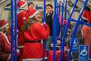 Participants arrive by tube - Thosuands of runners, of all ages, in santa suits and other Christmas costumes runaround Clapham Common for Great Ormond Street Hospital and for fun. London 30 Nov 2016