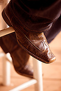 The cowboy boots of a musician rest on a stool while he plays his guitar.