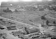 Ackroyd_00870-5. NW Yeon & 26th Ave. looking south. Left foreground is Dulien Steel 3190 NW Yeon, center and right foreground Industrial Air Products owned by Gilbert Schnitzer 3200 NW Yeon. In the background on the extreme left is US Steel 2345 NW Nicolai. In the center is the Calbag junkyard. The Calbag building is to the right of the yard, its the new two-story white building. The older building in the center with the smokestack is the old Portland Garbage Disposal Incinerator later to become West Coast Fast Freight. The vacant land in the center is the subject of this photo, it is the land on the south side of NW Yeon Ave. at the intersection of NW 26th Ave., which is address numbered in the 3200s.