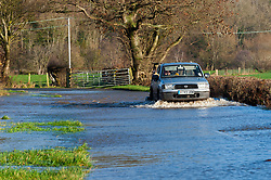 © Licensed to London News Pictures. 19/12/2020. Whitney-on-Wye, Herefordshire, UK. A farmer negotiates a flooded road at Whitney-on-Wye in Herefordshire. The river Wye breaks it's banks at Whitney-on-Wye, in Herefordshire, UK. Photo credit: Graham M. Lawrence/LNP