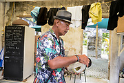Man picks bananas from the plantation in his house. Rarotonga, Cook Islands. December/2016.