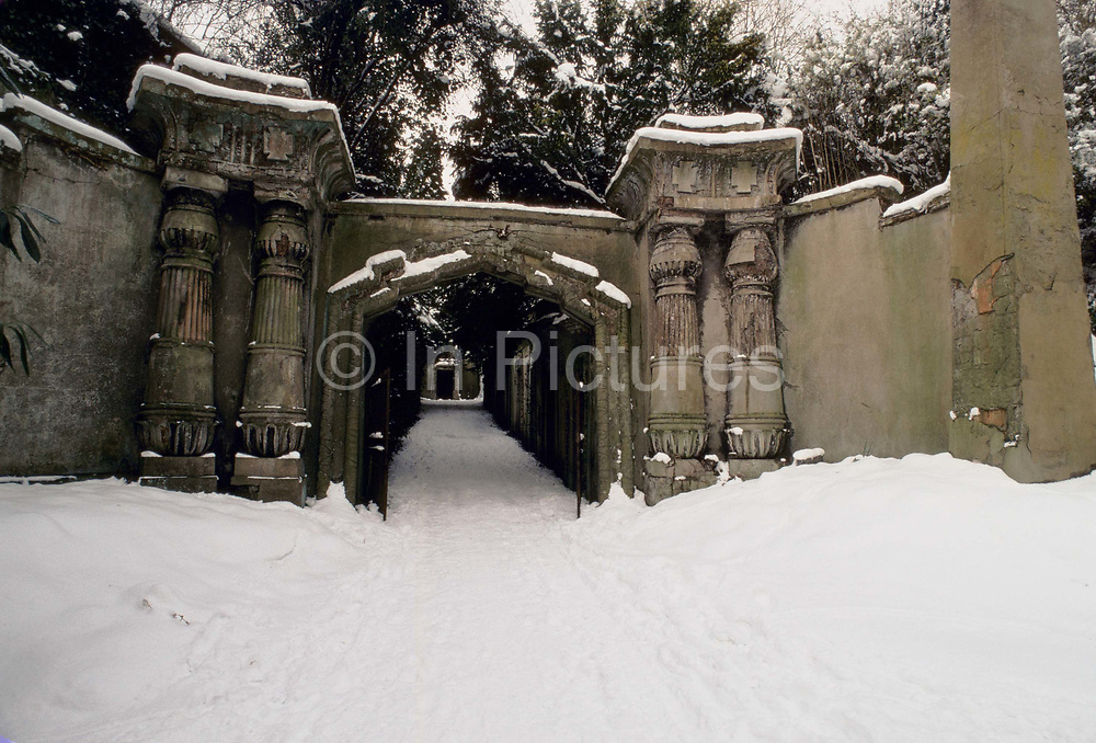 The Egyptian gateway in the snow, flanked by a pair of massive obelisks in Highgate Cemetery is the entrance to an avenue, lined with tombs, leading up to the Circle of Lebanon photographed in 12th December 1980, Highgate, London, United Kingdom. When the cemetery was founded in the 1830s interest in ancient Egypt was still very strong, encouraged by Napoleons campaigns.