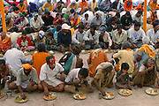 Thousands of pilgrims enjoy free meals of vegetarian curry and dal served by volunteers at Sri Swami Santdas Udaasin Ashram during the Hindu festival of Kumbh Mela, in Ujjain, India.  (From the book What I Eat: Around the World in 80 Diets.)