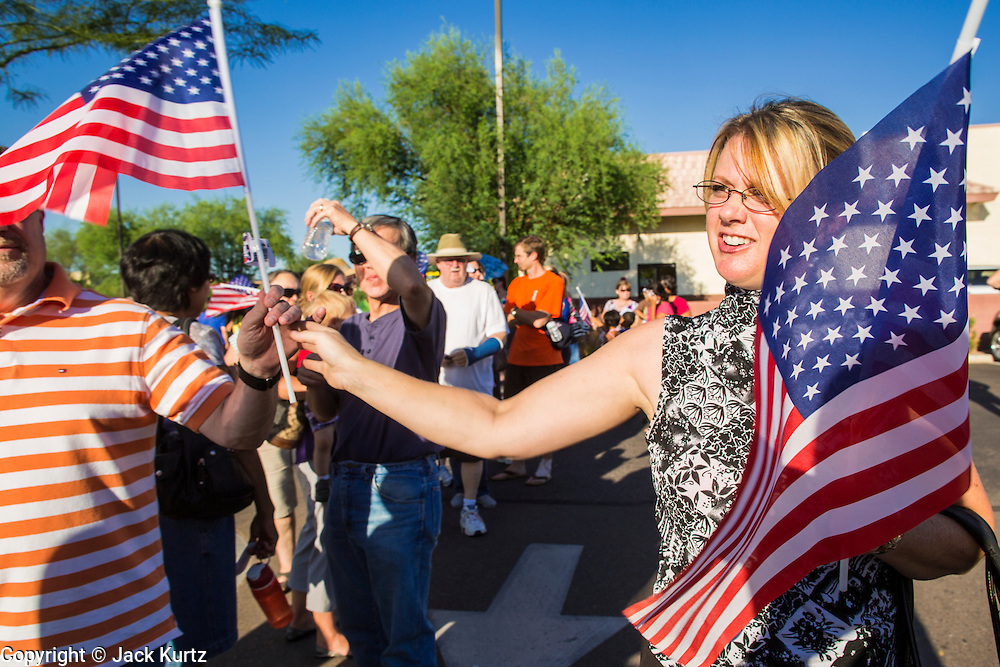 01 AUGUST 2012 - CHANDLER, AZ:  A woman passes out American flags at a Chick-fil-A Wednesday. Thousands of people stood in line for up to an hour at the Chick-fil-A in Chandler, AZ, a suburb of Phoenix Wednesday after MIKE HUCKABEE, the former governor of Arkansas and Fox News host, called for a national ''Chick-fil-A Appreciation Day,'' a day on which he encouraged people to patronize the fast food chain, this after DAN CATHY, President and CEO of Chick-fil-A, who is a fundamentalist Christian, made public his views against same sex marriage, causing an outcry from political leaders and Gay rights advocates.   PHOTO BY JACK KURTZ