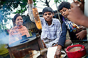 Sachin, 18, (centre) Poonam's oldest brother, is cooking corn the family is now selling, while sitting on his father's trolley, bought with part of the money donated by 'The Photographers Giving Back Awards' in 2011, in order to improve the family's quality of life, near their newly built home in Oriya Basti, one of the water-affected colonies in Bhopal, Madhya Pradesh, India, near the abandoned Union Carbide (now DOW Chemical) industrial complex.