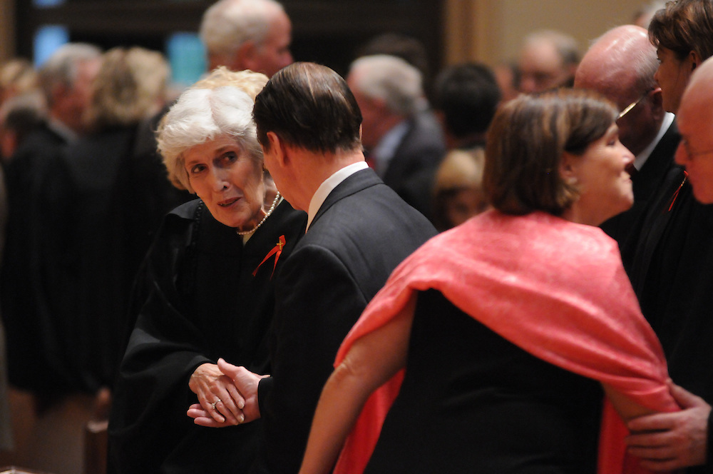 Retired Illinois Supreme Court Chief Justice Mary Ann McMorrow (L) shares a sign of peace with fellow attendees of the Catholic Lawyers Guild Annual Red Mass at Holy Name Cathedral, celebrated by Francis Cardinal George.