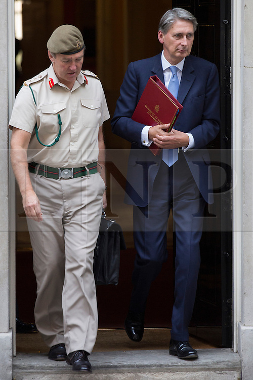 © licensed to London News Pictures. London, UK 28/08/2013. The Chief of the Defense Staff General Sir Nick Houghton (left) and Defence Secretary Philip Hammond leaving No10 on Downing Street, London on Wednesday, 28 August 2013 after attending a meeting of the National Security Council regarding the Syrian crisis. Photo credit: Tolga Akmen/LNP