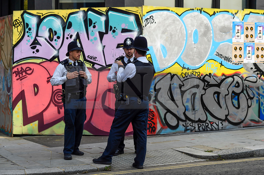 © Licensed to London News Pictures. 27/08/2018. LONDON, UK. Police stand by a boarded up premises of The Grand Finale parade at the Notting Hill Carnival.  Over one million revellers are expected to visit Europe's biggest street party over the Bank Holiday Weekend in a popular annual event celebrating Caribbean culture.  Photo credit: Stephen Chung/LNP
