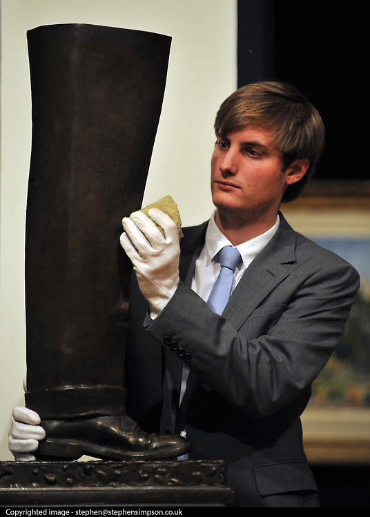 © Licensed to London News Pictures. 02/02/2012, London, UK. A gallery assistant polishes a sceptre by artist Rene Magritte. The item is expected to fetch 150,000-200,000GBP. Photo call at Bonhams, London for Impressionist and Modern Art Auction preview..  Photo credit : Stephen Simpson/LNP