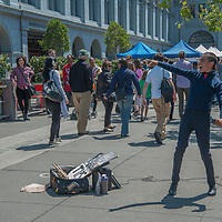 A street musician plays for Saturday crowds at the Embarcadero in downtown San Francisco, California.  Behind is the San Francisco Bay Bridge.