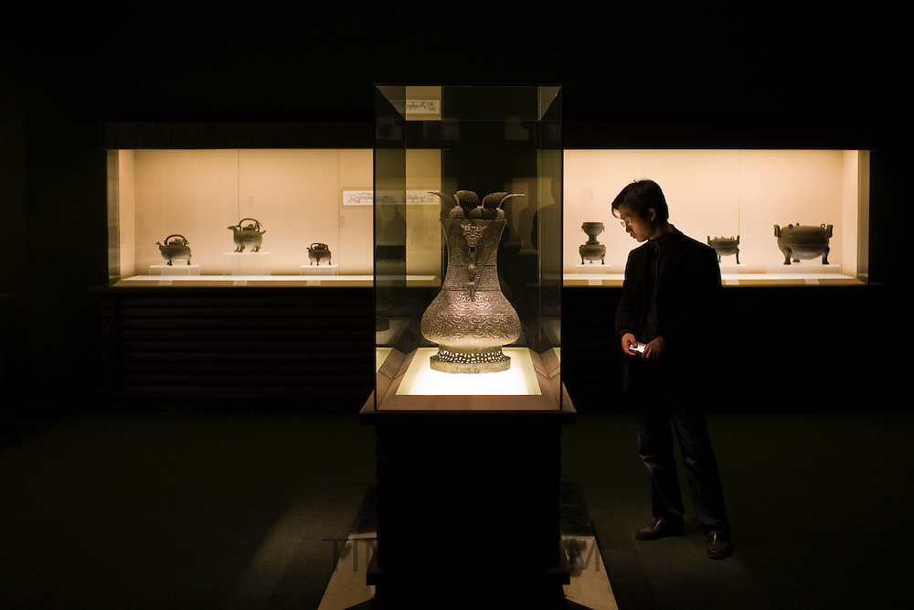 Man looks at a wine vessel on display in glass case at the Shanghai Museum, China