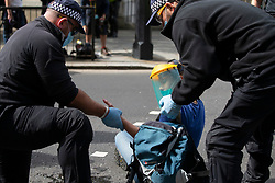 © Licensed to London News Pictures. 02/09/2020. London, UK. Specialist police remove glue from the hands of a Extinction Rebellion protester after she glued herself to the a road outside the Houses of Parliament . The environmental activist group have continued to block roads around parliament in an attempt to disrupt PMQs.  Photo credit: George Cracknell Wright/LNP