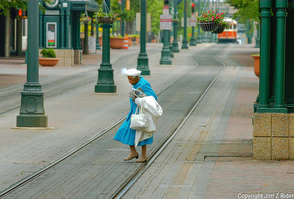 An elderly woman watches her step across railroad tracks as she strolls through downtown Memphis, Tennessee.