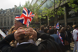 Haymarket, London, UK  29/04/2011. The Royal Wedding of HRH Prince William to Kate Middleton. Woman fixes a Union Jack flag to the back of her head, Haymarket. Photo credit should read PAUL TREACY/LNP. Please see special instructions. © under license to London News Pictures