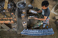 Top view of Laotian man making spoons in the 'Spoon Village' (Ban Napia), Phonsavan, Xieng Khouang Province, Laos, Southeast Asia. Since the late 1980's the people of this village have created spoons using aluminum UXO scraps left from the Indochina War.