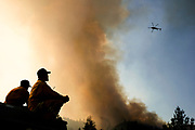 From left: Cal Fire HealdsburgÕs Andrew Rush and Charles Schindler watch as helicopters dump water down to the Kincade Fire off of Pine Flat Road on Friday, Oct. 25, 2019, east outside of Geyserville, Calif.