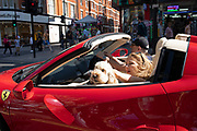Woman in a red Ferrari with her dog on her lap on Oxford Street in London, England, United Kingdom.