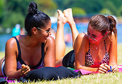 Friends Imogen Weston, 27 and Nicoletta Unito soak up the sun beside The Serpentine in Hyde Park as temperatures soar beyond the mid-30s in London. London, July 25 2019.