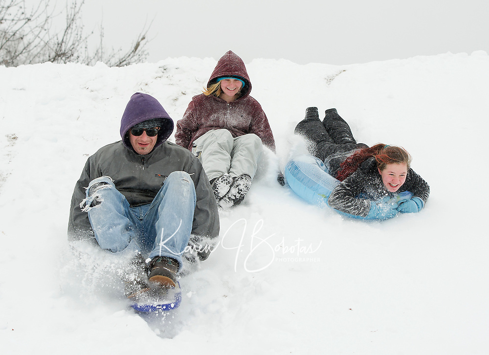 Phillip Hendrickson, Hailey Bolduc and Katrina Hanks dusted off their sledding gear and enjoyed new snow off Blueberry Lane in Laconia on Tuesday morning.  (Karen Bobotas/for the Laconia Daily Sun)