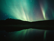Aurora and Sheep Mountain reflected in Knob Lake the night of September 26, 2001, Tahneta Pass, Alaska.