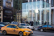 An iconic New York yellow taxi and other cars drive past Apple Inc's flagship Apple Store on 5th Avenue, New York City, New York, United States of America.