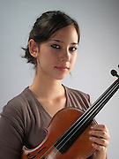 young female violinist holding her violin, studio shot Model released