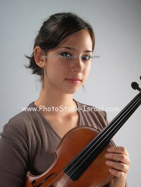 young female violinist holding her violin, studio shot Model released