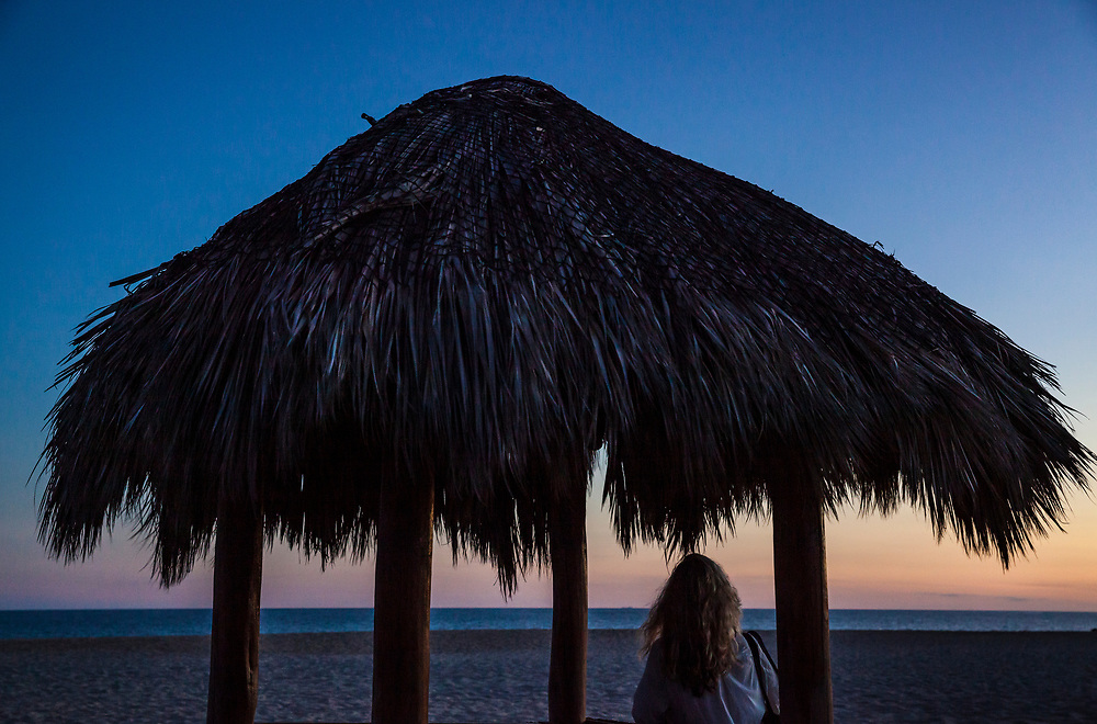 A blond woman stands under a thatched roofed shelter at sunset on Costa Azule, San Jose del Cabo, BCS, Mexico.