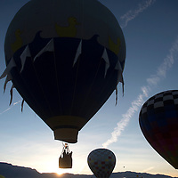 Ballons take off during the Farewell Ascension of the Albuquerque International Balloon Fiesta, Sunday while the Sun rises over the Sandia Peaks in the distance.