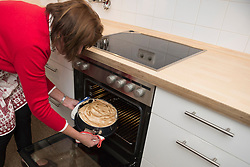 Senior woman taking out baked cake from oven, Munich, Bavaria, Germany