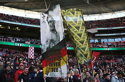 Arsenal fans wave flags in the stands ahead of the match