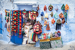 Colorful hats and textiles for sale against blue wall, Chefchaouen, Morocco