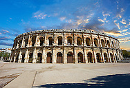 Arena of Nemes, a Roman Ampitheatre built around 70 AD during the reign of Emperor Augustus, Nimes, France . The Arena of Nîmes is a Roman amphitheatre, situated in the French city of Nîmes. Built around 70 CE, shortly after the Coliseum of Rome, it is one of the best-preserved Roman amphitheatres in the world.  The Arena of Nîmes is 133 meters long (145 yards) and 101 meters wide (110 yards), with an arena measuring 68 meters (74 yards) by 38 meters (32 yards). The outer facade of the Arena of Nîmes is 21 meters high (69 feet) with two stories of 60 arcades. .<br /> <br /> Visit our ROMAN ART & HISTORIC SITES PHOTO COLLECTIONS for more photos to download or buy as wall art prints https://funkystock.photoshelter.com/gallery-collection/The-Romans-Art-Artefacts-Antiquities-Historic-Sites-Pictures-Images/C0000r2uLJJo9_s0