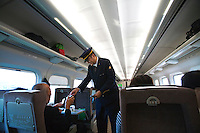 Bullet Train Conductor Checking Tickets - The Shinkansen is a network of high-speed railway lines in Japan operated by JR or Japan Railways.  Starting with the 210km/h Shinkansen in 1964 the now 2,500 km long network has expanded to link most major cities on the islands of Honshu and Kyushu at speeds up to 300km/h.
