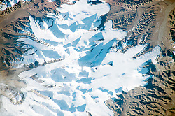 A long lens and low sun angle allowed an astronaut to take this striking photograph as the International Space Station flew over the remote desert landscape of northern Tibet. Sunlight reflects brilliantly off the ice of several glaciers in one of the highest sectors of the Kunlun Mountains. The major peaks of the mountains cast dark, pointed shadows in mid-afternoon. The surrounding landscape is a nearly barren, dun-colored desert.<br /> Mountains tend to look flat from orbit, particularly when viewed from directly above. The mountain in the center of the image - Ulugh Muztagh - appears insignificant. But being the highest (6,973 meters or 22,877 feet) peak, it casts the longest shadow, which helps astronauts get a three-dimensional sense of the landscape. If this were an unmapped planet, the length of the shadows could be used to calculate the height of each mountain peak (assuming you knew a ground distance and the Sun angle).<br /> The low sun angle reveals rough textures at the snout (terminal) end of the glaciers, which otherwise appear remarkably smooth. Rough textures show where the ice is melting fast. Although the peaks receive very little precipitation (less than 5 inches or 13 centimeters per year), the cold desert preserves more snow than can melt on the highest, coldest parts of the mountains. The preserved ice slowly accumulates and begins to flow very slowly downhill, away from the high peaks. At the snout of the glaciers, melting at the warmer low altitude balances the flow of ice from the mountain peaks.<br /> One other area of glacier roughness (lower left), however, is not located at the snout end of the glacier. This is a region of crevassing, where glacial ice is splitting to make deep clefts. It is likely because the ice is flowing faster over a steeper part of the valley.<br /> Astronaut photograph ISS045-E-53329 was acquired on October 10, 2015, with a Nikon D4 digital camera using a 500 millimeter lens, and is provided by the ISS Crew Earth