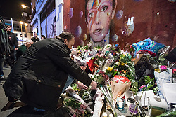 © Licensed to London News Pictures. 10/01/2017. London, UK. A man lays flowers beneath a mural of David Bowie in Brixton, south London, to commemorate the first anniversary of the star's death. Photo credit: Rob Pinney/LNP