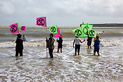 Members of Extinction Rebellion take part in an Art Action on Sunny Sands beach, Folkestone, United Kingdom on the 25th of August 2020.  Adults and children walked into the sea fully clothed today with banners and placards to highlight the changing climate crisis we are living in and to highlight sea levels rising. Coincidently climate change was in action at the same time with storm Francis raging with high winds and severe rain. <br /> (photo by Andrew Aitchison / In Pictures via Getty Images)