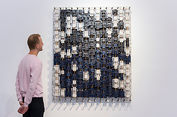 """© Licensed to London News Pictures. 12/10/2021. LONDON, UK. A staff member views """"Paradise and regret"""", 2021, by Jacob Hashimoto. Preview of a new exhibition by Jacob Hashimoto at Ronchini Gallery in Mayfair.  The New York-based artist's continuing interest in kite-making is presented via a collection of paper """"kites"""" in undulating, interactive compositions.  The show runs 13 October to 23 December 2021.  Photo credit: Stephen Chung/LNP"""