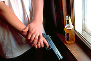 Man age 21 with his beer holding 45 pistol and looking out window MR.  St Paul Minnesota USA