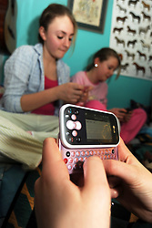 Teenage girls text on mobile phones at a sleepover